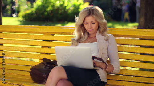 Young adult woman girl types message laptop chatting smiling