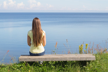 Young woman sitting on bench facing the sea