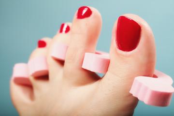foot pedicure applying red toenails on blue