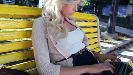 Woman sitting on bench typing in park with laptop, stedicam