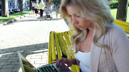 Pan tilt young woman with laptop in park, social network
