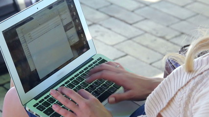 Laptop screen young woman hands type letter e-mail in park