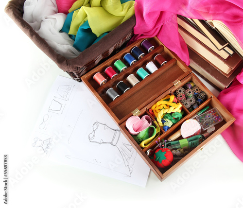 Sewing kit in wooden box with books and cloth isolated on white