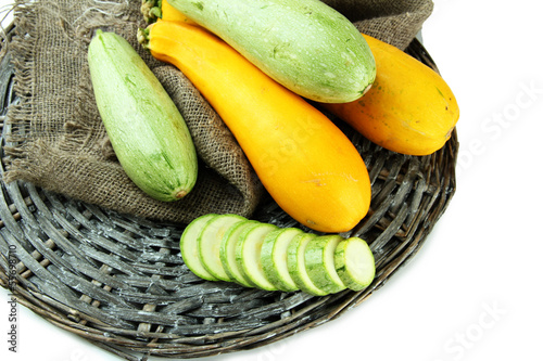 Sliced and whole raw zucchini, isolated on white
