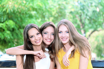 Three beautiful young woman  sitting on bench in summer park