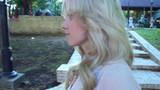 Blonde pretty woman walking in park follow camera, smiling, shy