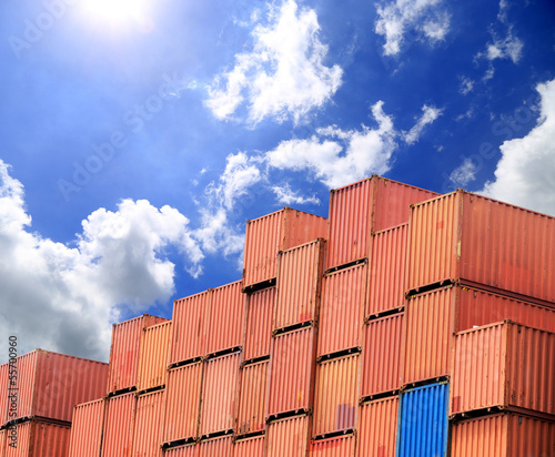 Stacked cargo containers in storage area with blue sky