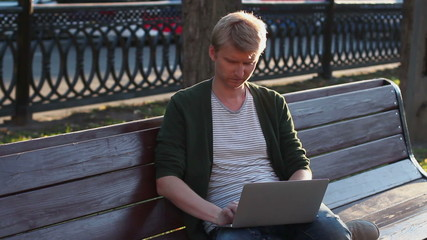 Man in park working laptop reading and writing messages browsing