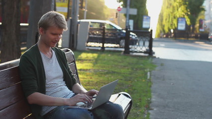 Young blond adult male types on laptop turns smile, success