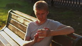 Young blond adult man writing sms message in park bench