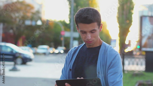 Young adult male browsing tablet pc computer, looking at camera