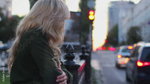 Depressed young woman standing near fence with moving traffic