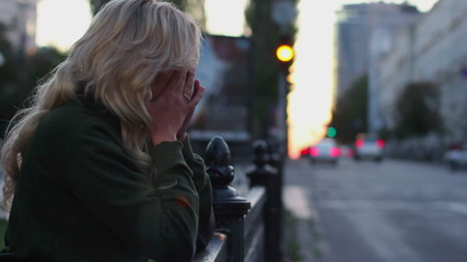 Woman hands on face cries for broken relationships, traffic cars