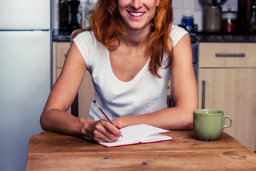 Happy woman writing in her kitchen