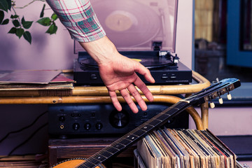 Man pickingup guitar after listening to records