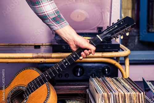 Hand picking up guitar next to box of vinyl