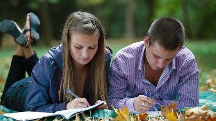Friends studying in autumn park