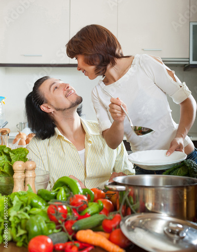 Handsome man and beautiful woman with vegetables in the kitchen