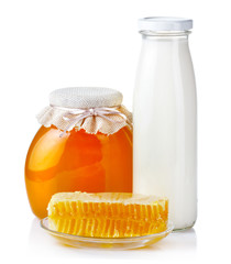 Sweet honey in glass jars with honeycombs and bottle of milk iso