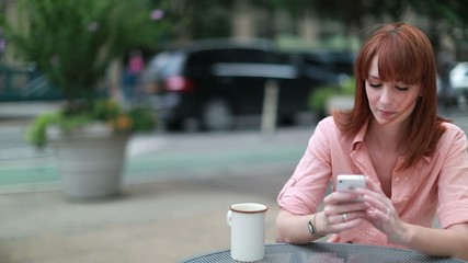 Caucasian woman using cellphone texting outdoor