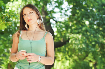 Girl listening to music with earphones in a park, sunny day