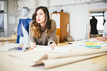 Pensive fashion designer drawing in studio