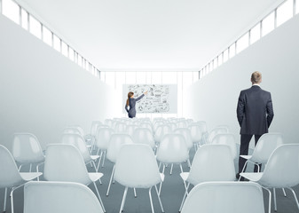 Businesswoman and businessman standing in meeting room