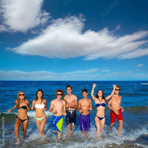 Teens group running happy splashing on the beach