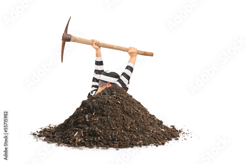 Male prisoner digging a hole and trying to escape