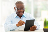 Fototapety senior african american man using tablet computer at home