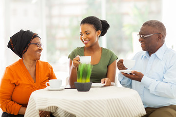 senior african parents having coffee with daughter