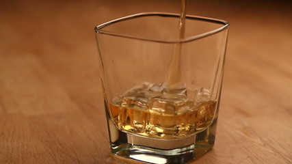 Pouring brandy or whiskey with ice cubes into the glass