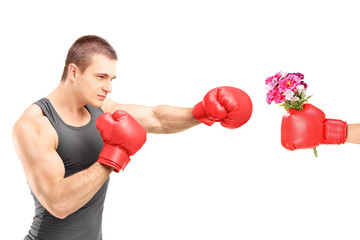 Male athlete with boxing gloves hitting a hand with boxing glove