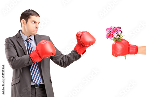 Angry man with boxing gloves hitting a hand with boxing glove