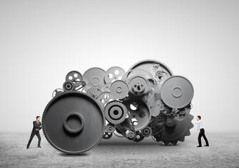 two businessman pushing metal gears