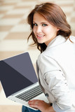 Young smiling woman sitting with laptop computer