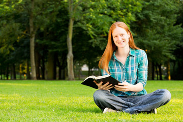 Young Believer with a Bible in a Park