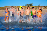 Teen surfers group running beach splashing