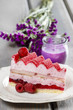 Pink layer cake decorated with fresh fruits on wooden table