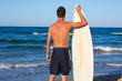 Boy surfer back view holding surfboard on beach