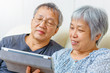 Asian elderly couple using digital tablet