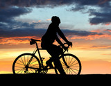 silhouette of the cyclist on road bike at sunset