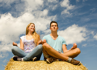Junger Mann und junge Frau meditieren im Freien