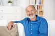 älterer mann sitzt entspannt auf dem sofa