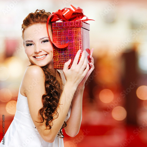 Happy young woman with birthday present in hands