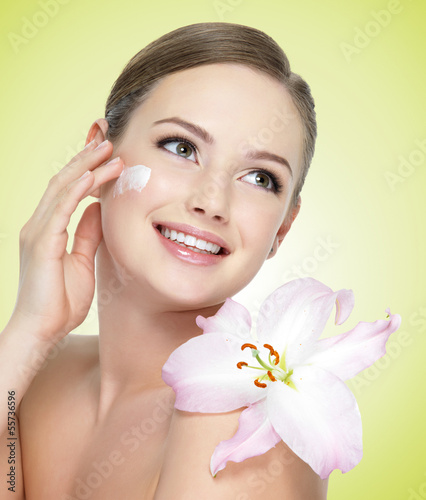 smiling woman with flower  applying cosmetic  cream on  face