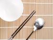 asian dish place setting on bamboo mat