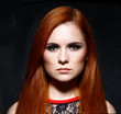 Young beautiful red hair woman in dark studio