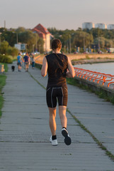 Sportsman running near the sea. Back view.