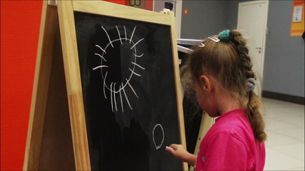 little girl drawing sun with chalk on blackboard